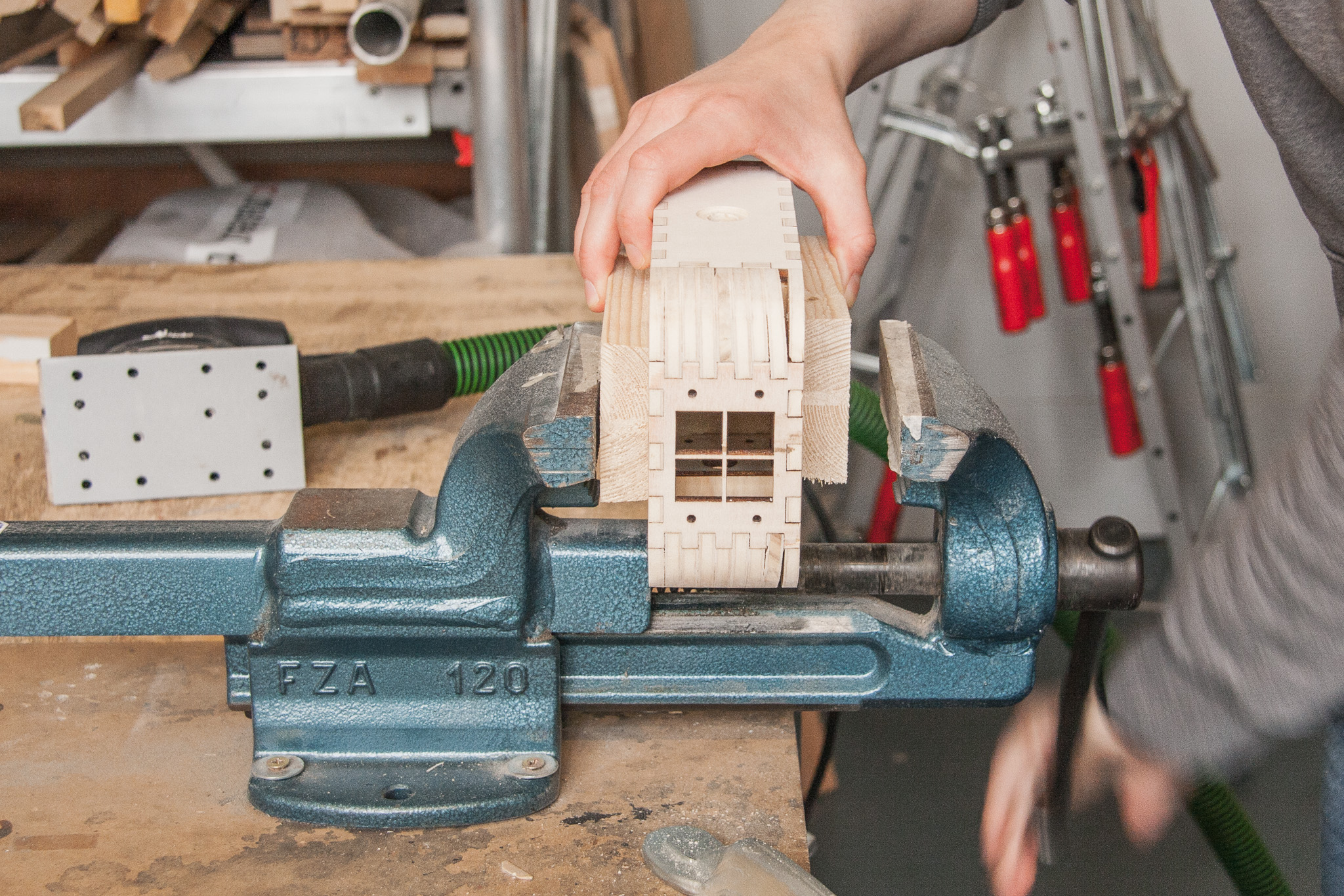 Fix the box in a vise with wooden blocks to protect it from dents.