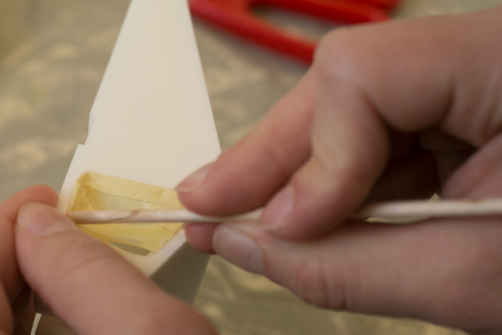 A pointy wooden stick helps when applying tape to tricky areas